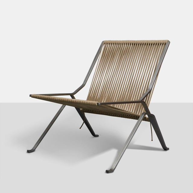 A PK-25 lounge chair with matt chromed spring steel frame made using a single piece of steel, mounted with woven flag...