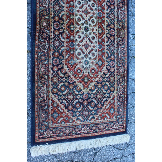 """Long rectangular traditional hallway rug of red and white geometric figures on blue background with white fringe. 57""""..."""