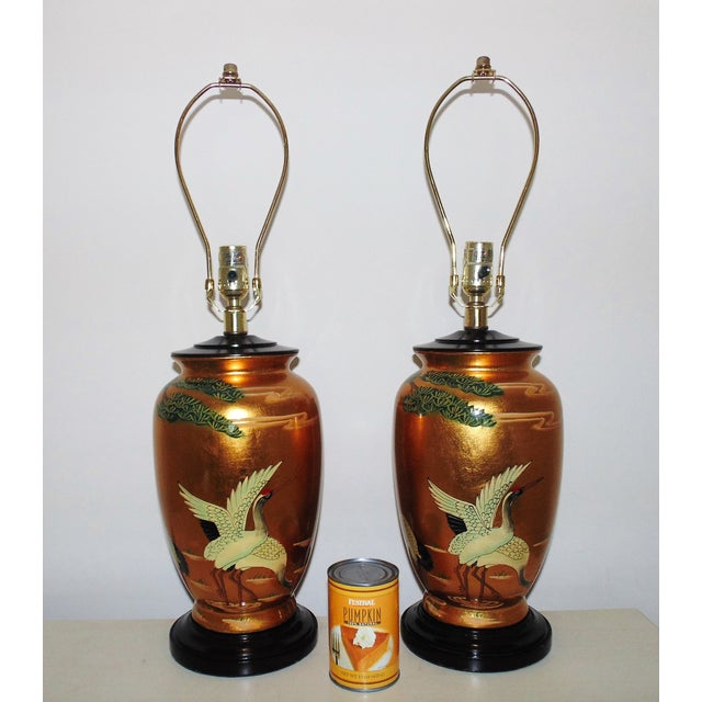 This is a fabulous pair of Chinese table lamps. Ceramic base with wood cap and stand. Features hand-painted herons in...
