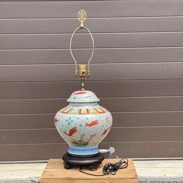 A quality vintage porcelain lidded ginger jar lamp decorated with Koi complete with harp and brass finial. Shade not...