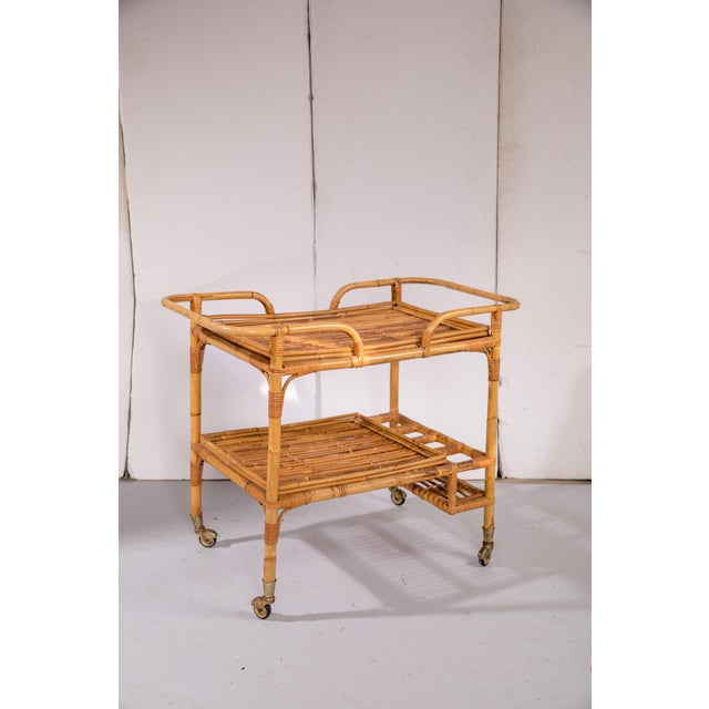 1950s rattan bar cart. Glass inserts for the top and bottom shelves create a level surface for corralling supplies. The...