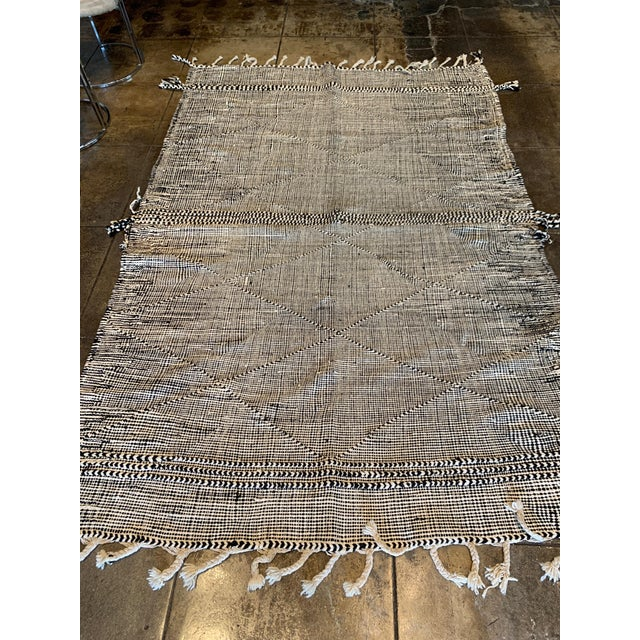 Contemporary style black and white area rug with tassels. Made in Marrakech and found at Paris Home Show.