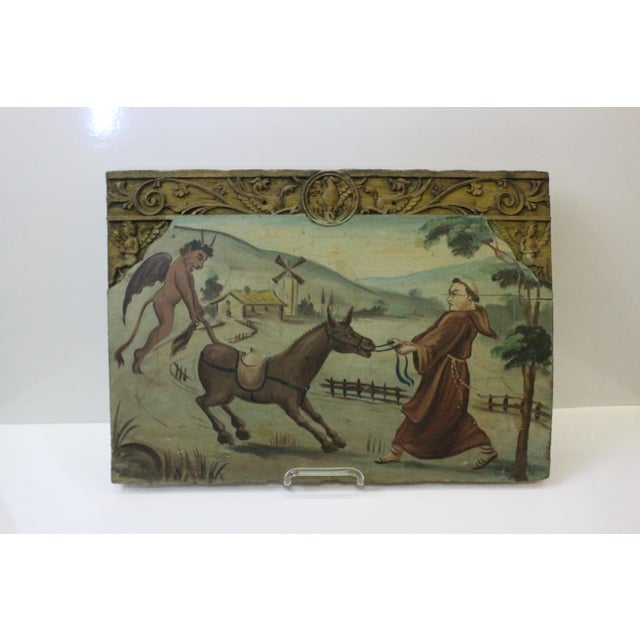 Antique Late 18th Century carved wood with painting of a Franciscan monk and the devil battling over a mule.