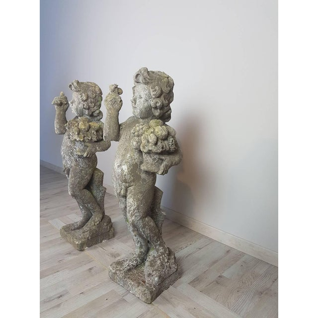 Beautiful refined pair of garden statues in neoclassical style. Two very sweet children. Made in the 1950s in cement....
