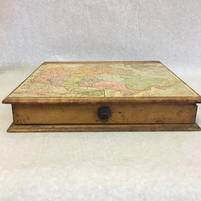 A decorative box with one drawer and a map on the top.