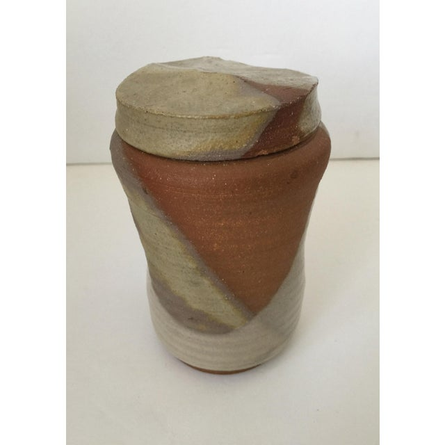 Mid Century Modern Artisan Pottery Covered Jar Lovely stonewear covered jar. Base has a small handle with indents on sides...