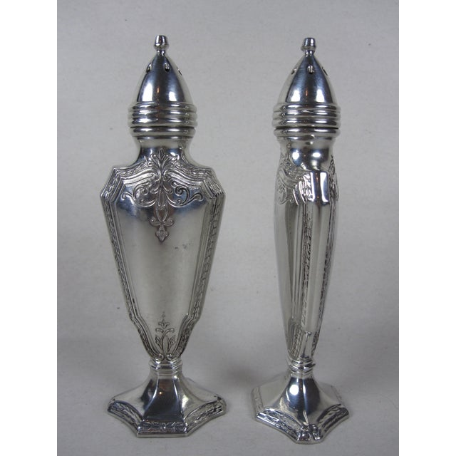 An unusual and weighty pair of Art Deco-style, silver-plated salt and pepper shakers. Flat sided and footed, these shakers...