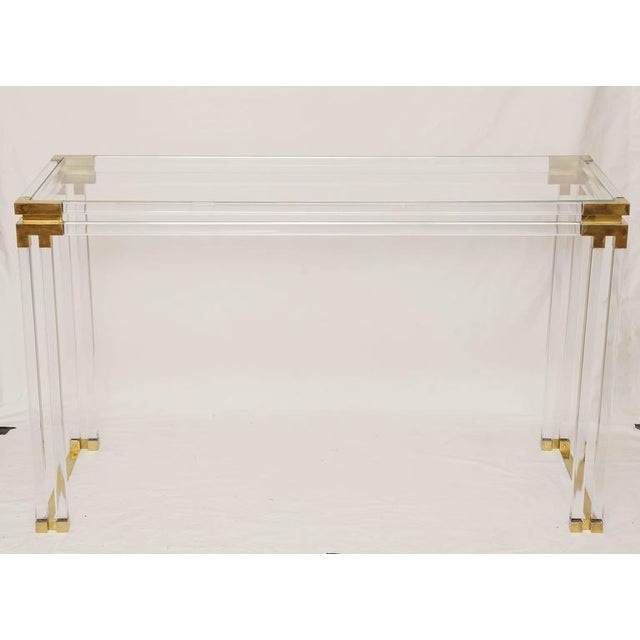 A simply gorgeous Lucite glass console table with brass details styled after Charles Hollis Jones. The glass top sits on...