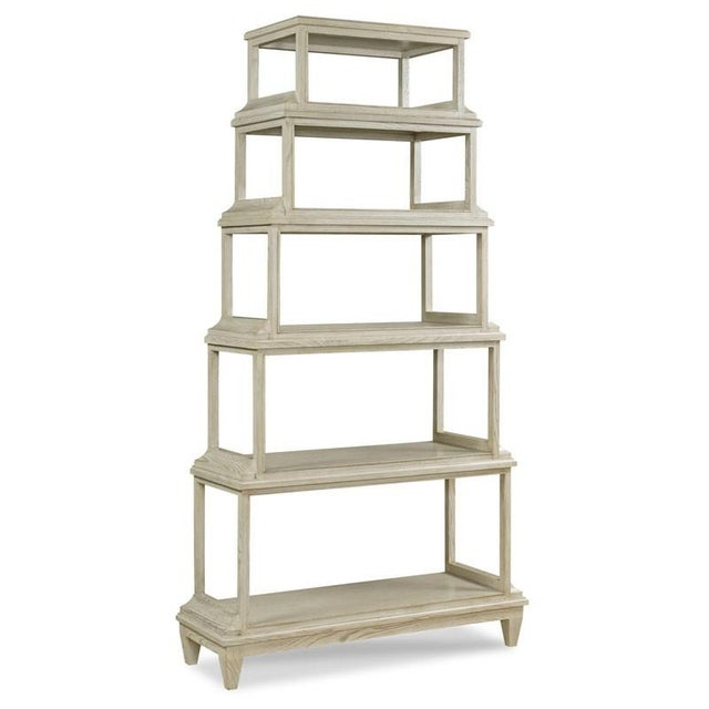 Five graduating shelves are veneers with ash that rest over a base with tapering legs. Crafted from hardwood solids and...