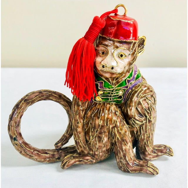 Set of four large scale cloisonné napkin rings in the shape of sitting monkeys.