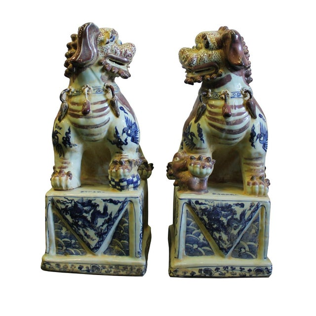 This is a pair of precisely made porcelain Foo Dogs in off white base color and blue color graphic and fade red hair color...