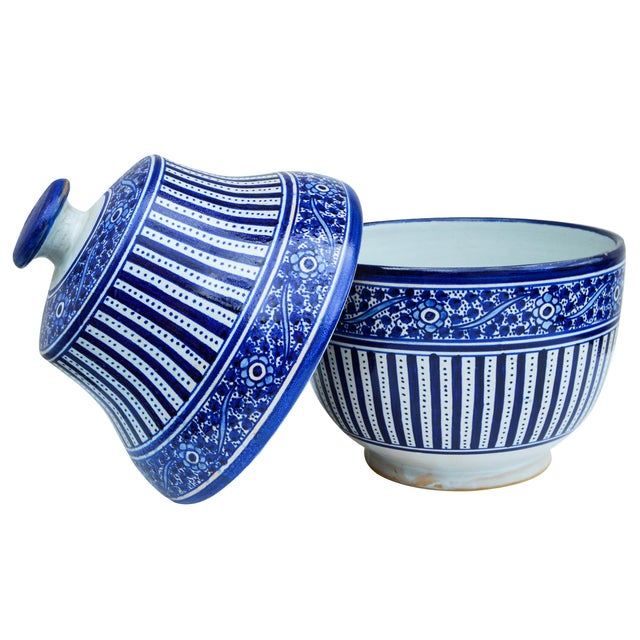 Handcrafted and glazed Moroccan ceramic bowl with lid. Features a hand-painted floral pattern in blue hues. Maker's mark...