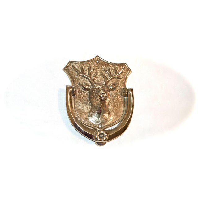 A fine brass door knocker featuring a handsome stag on a shield-shaped background. The knocker arm is decorated with a...