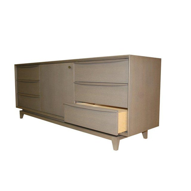 M|n Originals Grey Oak 6 drawer credenza with center retractable door on solid inset tapered leg base.Sculpted handles...
