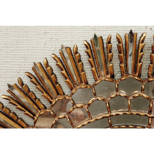 A brilliant giltwood sunburst mirror. A large mirror in the center is framed with smaller mirrors that fan out like...
