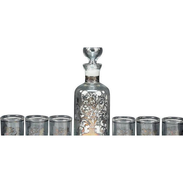 An italian bicchielli liquor suite. Comprising a decanter and six glasses all decorated with silver overlay decanter...