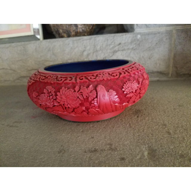 This is a Chinese bowl, hand carved and lacquered in cinnabar red with a very unique blue enamel interior, and a brass edge.