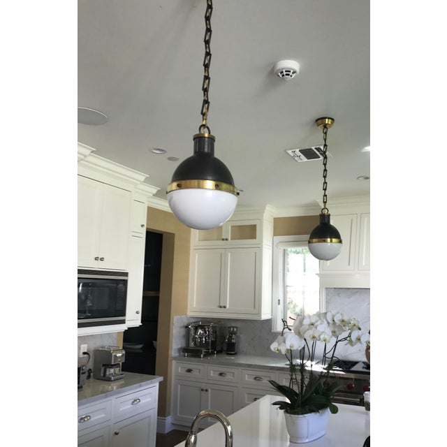 One pair of beautiful small-size Hicks pendant lights from Visual Comfort. Finish is Bronze with Antique Brass Accents...