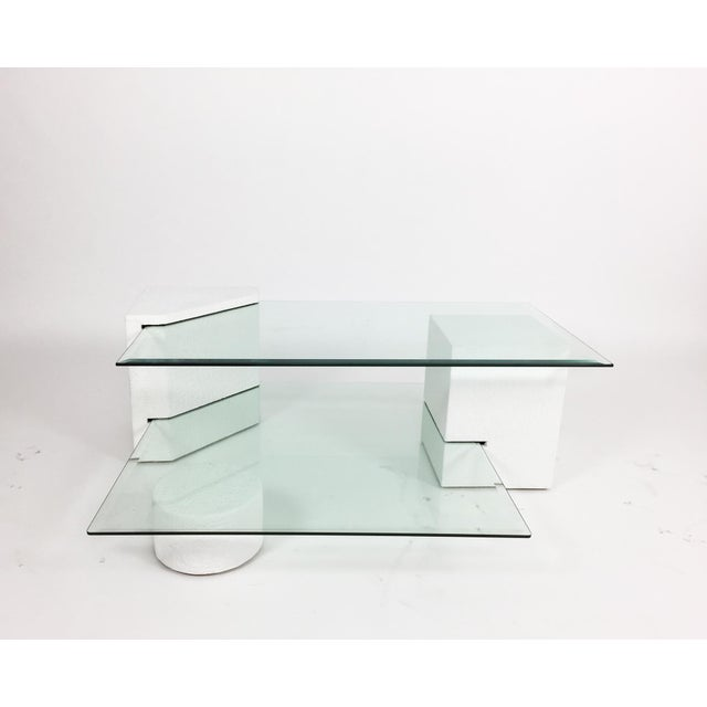 Multi-tiered coffee table composed of three geometric forms supporting two beveled glass sheets. Geometric elements are...