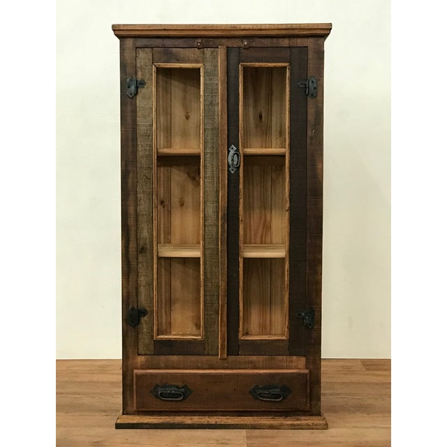 Designed for small spaces, this rustic Vitrine Display Cabinet features glass doors, three shelves, and a wide bottom...
