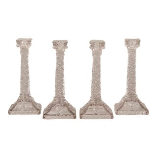 A set of four tall matching pressed glass candlesticks with an elaborate design from Belle Epoque period France c.1890.