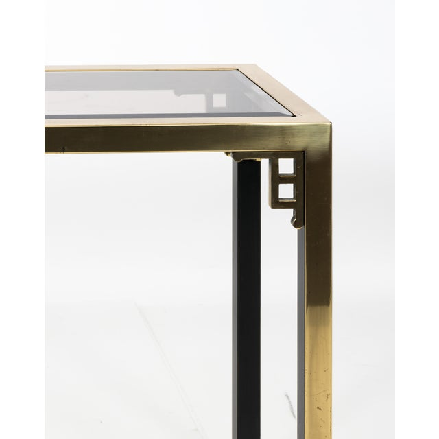 1970s brass Greek key motif console table. Original smoked glass with bevelled edge. Inside of console legs are painted...