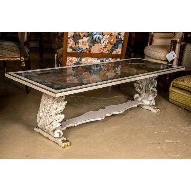 Attributed to Jansen, this elegant coffee table features a shell and leaf-carved base that supports a Verne Églomisé,...