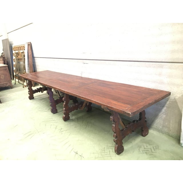 A monumental early 19th century Italian trestle table, having a rectangular framed solid walnut inset board top, resting...