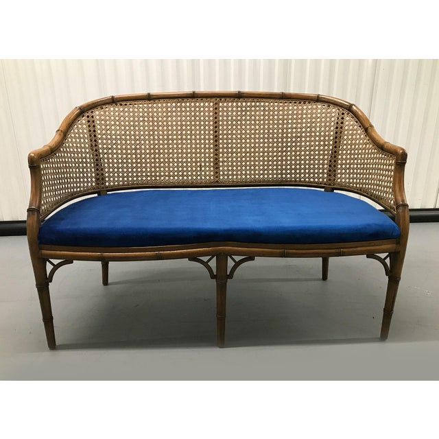 Stylish caned-back settee, circa 1960s. Newly upholstered in blue velvet fabric. Graceful lines, sturdy construction....