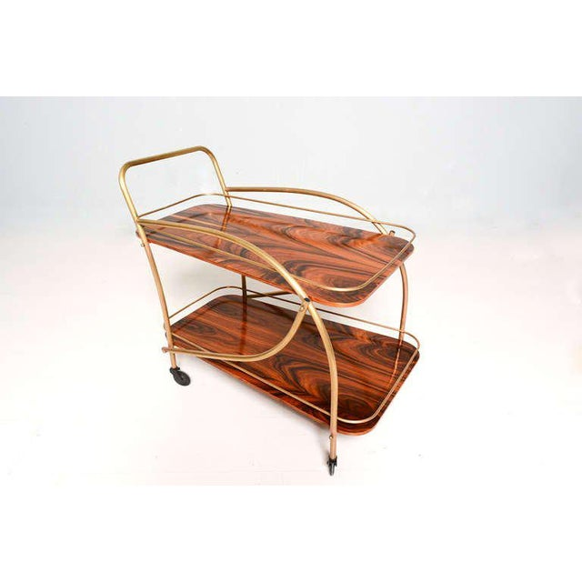 A beautiful Brazilian Rosewood Double Deck Service Cart presented in brass frame and guard rails. Original wheels.