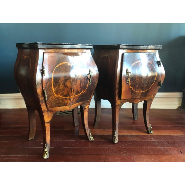 Pair of bombe nightstands or end tables with marquetry inlay, ormolu decorative leg caps and pulls and black glass tops....