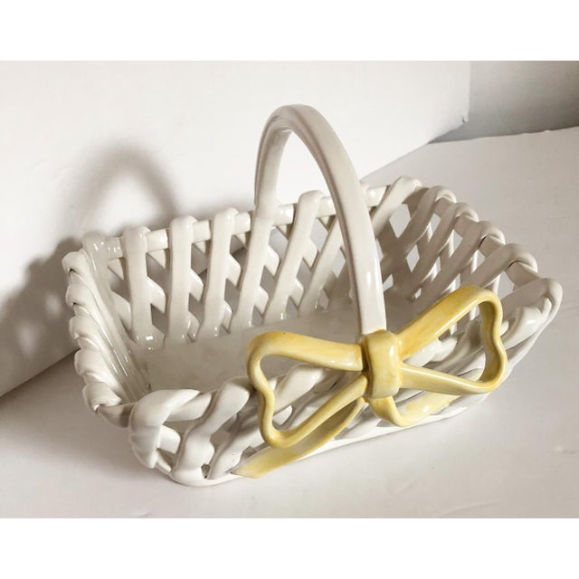 White ceramic woven basket with a yellow bow on the front, made in Portugal.