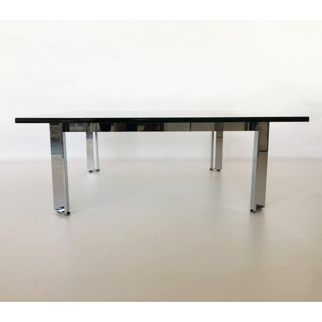 Architecturally inspired square coffee or cocktail table of chromed steel base with glass top.
