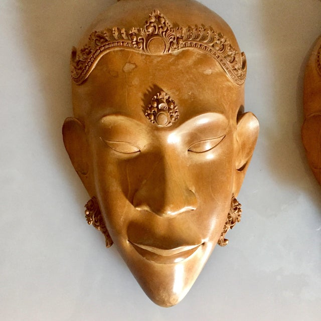 "Pair of intricately carved wooden masks from Vietnam circa 1970s. Each mask measures approximately 6"" wide and 11"" tall...."