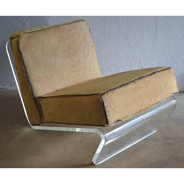 Great pair of bent lucite lounge chairs with original buff colored cow hide and contrasting black leather welt box...