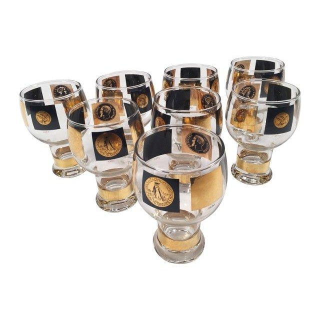 Add some authentic Mid-Century style to your bar with this unique set of eight bulb-shaped glasses with coin emblems.