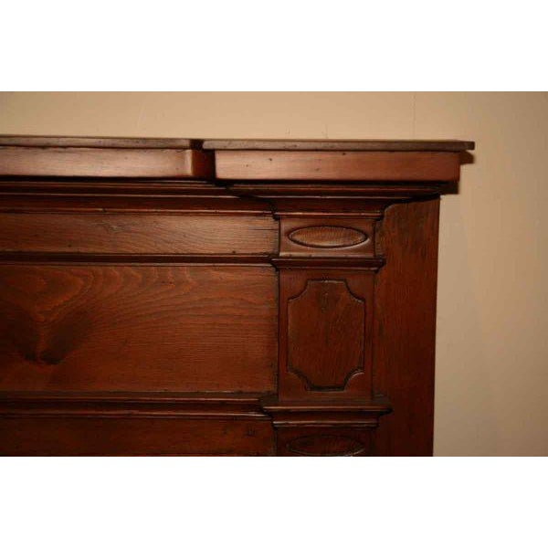The shelf has projections on both sides, with very simple detail on the sides and fluted pilasters on the jambs. It...
