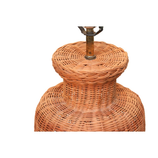 A wicker lamp woven in a traditional vase shape complete with round foot and plaited rimmed neck. A central brass column...