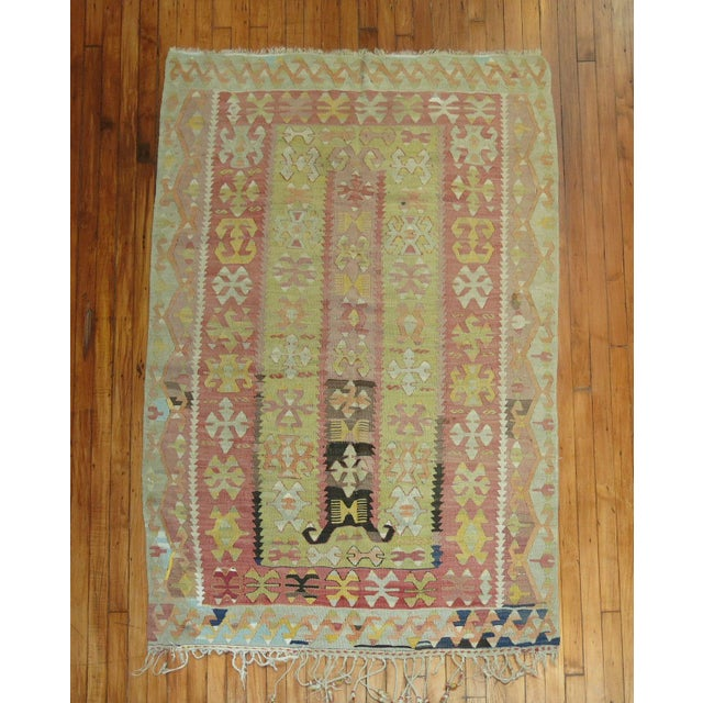 Offered is a hand-knotted vintage Turkish kilim rug. Colors are predominantly soft pink and soft green.