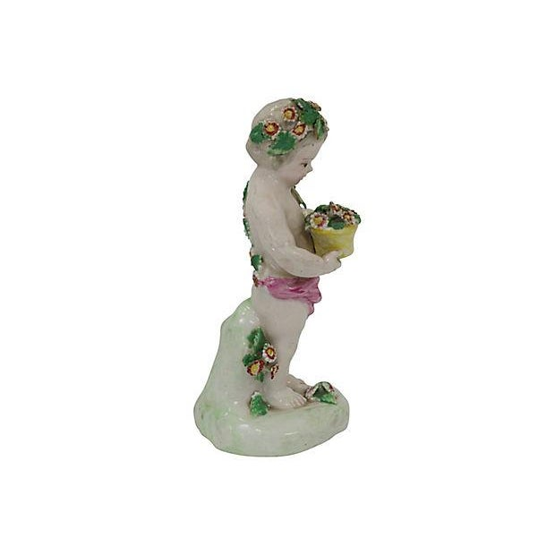 """Antique Derby porcelain cherub figurine with flower basket. The underside bears the """"pad marks"""" of early Derby (marks..."""