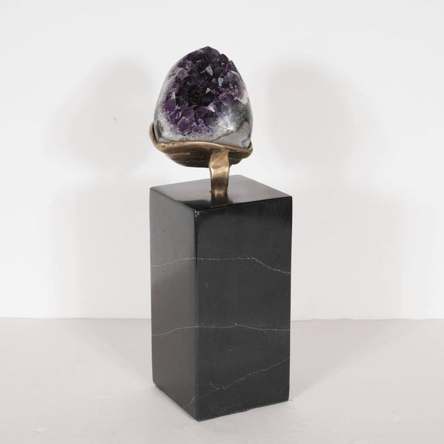 This striking amethyst offers a calyx of vibrant purple crystals. Since it is an exposed geode, its back consists of a...