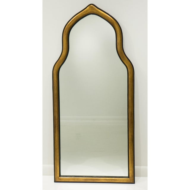 Handcrafted pier or wall mirror with a Moorish arch. Carved wooden frame with patinated gilt gesso and paint. Made by...