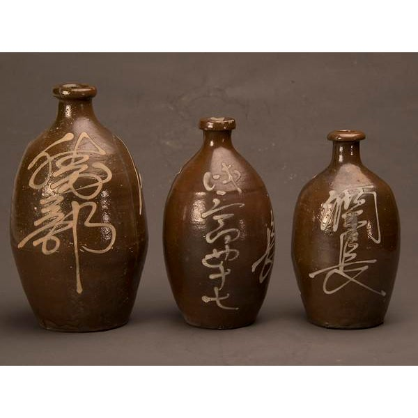 A trio of hand-made earthenware saki jars from Japan c. 1900. Each jar has a different signature in script across the...