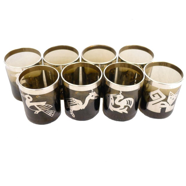 Set of 8 small smoke glass tumblers/glasses with a silver overlay in a Mayan/Aztec/Inca design. Condition consistent with...