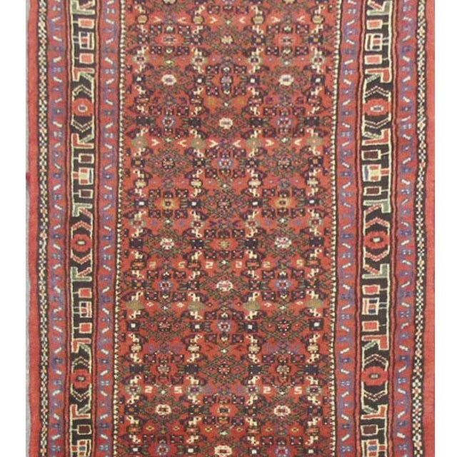 This beautiful rug is hand made, made in Iran. It features a pattern in a vibrant combination of red, navy, blue, purple....