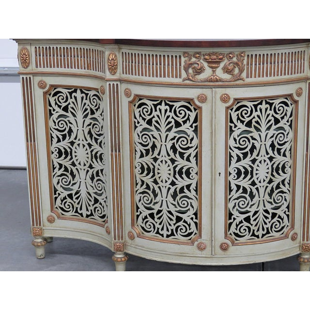 Adams style distressed paint decorated commode with gilt accents, pierced wood front and 2 doors containing 2 shelves.