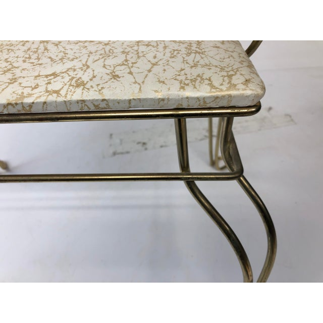 Vintage Vanity Stool. Original brass over steel construction with vinyl seat. Vinyl is white with a gold metallic design....