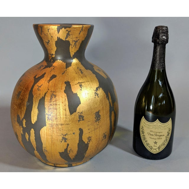 This gold leaf and charcoal gray painted vase is a stunning example of how a simple shape inspired by nature can be...