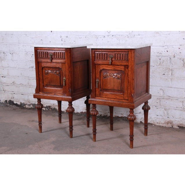 An exceptional pair of 19th century Victorian carved solid oak nightstands. The nightstands feature gorgeous oak wood...