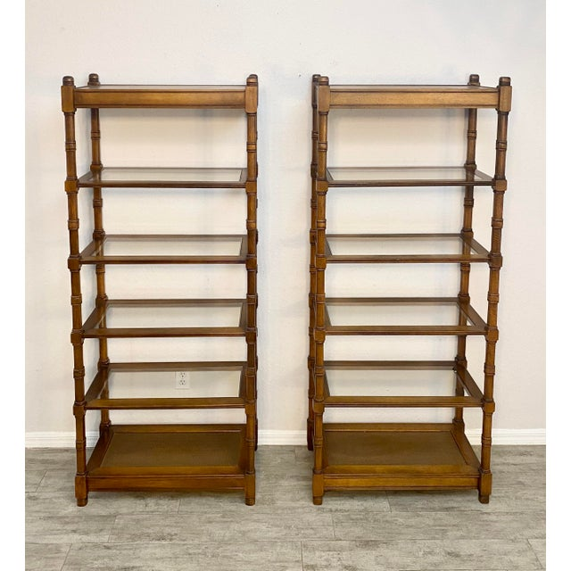 Pair of mid century modern etageres in like new condition. Solid wood frame, 4 glass shelves and bottom self in cane....